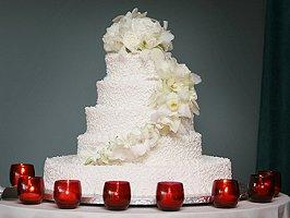 Elaborate wedding cake surrounded by red votives