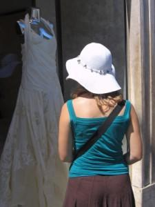 Woman looking at a wedding gown in a shop window