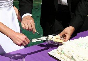 Couple cutting wedding sheet cake.