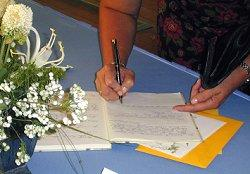 A wedding guest signing the guest book
