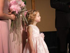 A flower girl standing with the bridesmaids