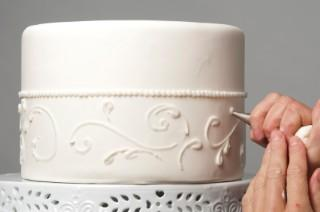 Piping decorations on fondant-covered wedding cake