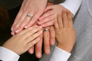 Hands of the bride, groom, and their children