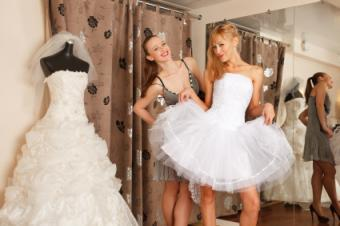 bride trying on short reception dress