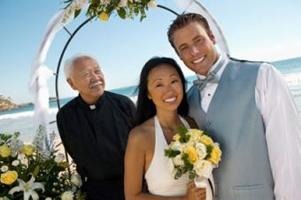 Hawaii beach wedding with bride and groom with priest under archway