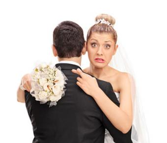 Bride hugging husband with fingers crossed