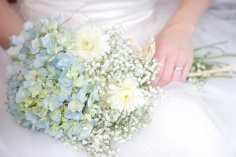 bride holding pale blue hydrangea bouquet