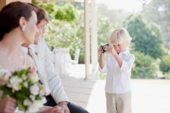 Boy taking picture bride and groom