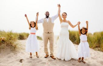 Bride and groom cheering with flower girls