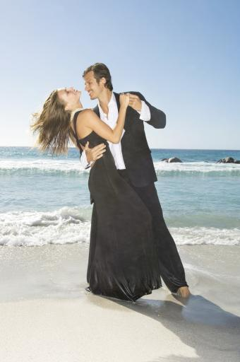 Man in suit dancing with blond woman in black evening gown on a sandy beach