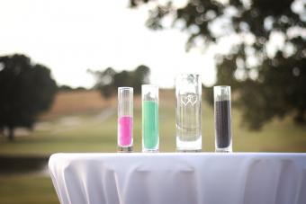Containers of colored sand on table