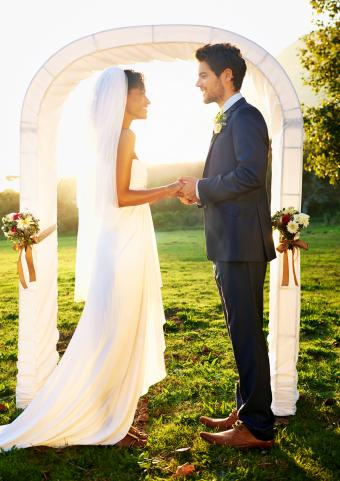 Bride and groom standing outside in front of the wedding arch