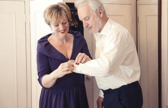 Woman buttoning senior man's shirt