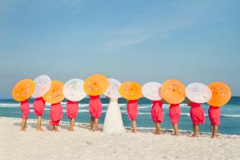 Bride with her bridesmaid holding parasols on the beach