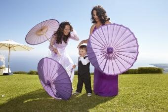 Two ladies carry purple paper parasols