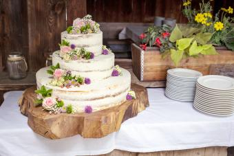 White Wedding Cake with pink Roses and Flowers on a cut Tree