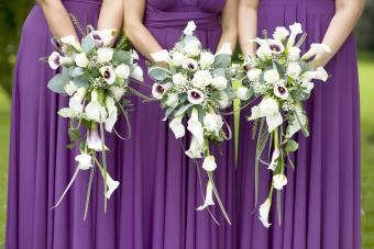 Three bridesmaids holding wedding bouquets