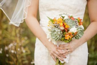 Bride holding wedding bouquet with Echeveria, Dahlia, and mini Hydrangea