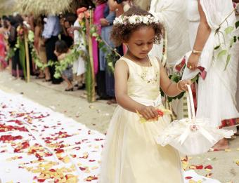 Flower girl in aisle dropping flower petals