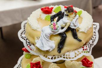 wedding cake with playful bridal couple as figure on top