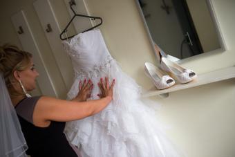 Bride touching wedding dress