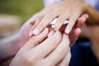 Young man is seen slipping an engagement ring on his girlfriend's ring finger