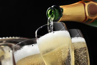 Pouring champagne into fluted glasses