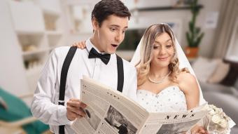 Newlywed couple reading newspaper