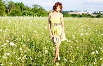 Woman in a field dressed for a barn wedding