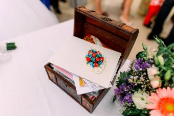 Wooden box for wedding money envelopes on table with colourful flowers
