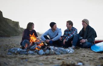 friends sitting around open fire