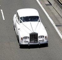 Luxurious white Rolls Royce limo on the road