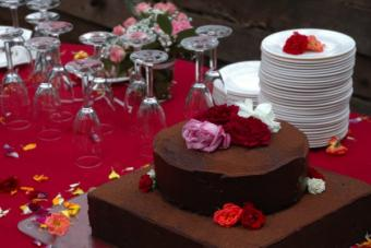 Groom's table with a cake, plates, and glasses