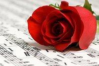 Red rose laying on wedding sheet music