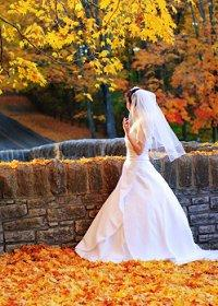A bride strolling through autumn leaves in the park