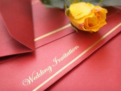 Red wedding invitation and a yellow rose