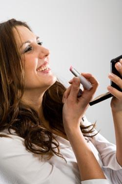 Woman applying lipstick using a compact mirror