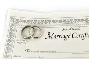 A marriage certificate and two silver wedding bands