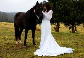 A bride petting a horse in a field