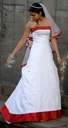 A bride in a white gown trimmed in red