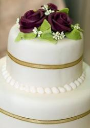 Wedding cake with gold ribbon and purple roses