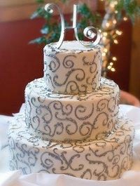 3-tier wedding cake with silver swirls and topper