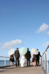 Bridal party on the boardwalk with parasols