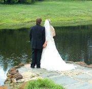 Bride and groom looking at a pond in a park