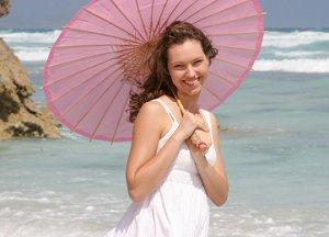 Bride on the beach with a pink parasol