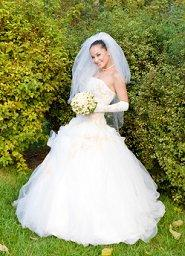 Bride posing in front of hedges at a backyard wedding