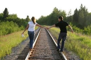 Couple holding hands walking on train tracks