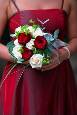 Bridesmaid in a red dress and carrying a rose bouquet