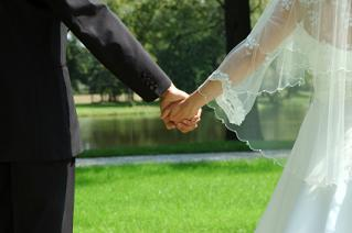 Bride and groom holding hands at their garden wedding