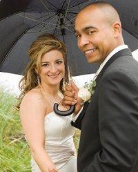 Bride and groom sharing an umbrella
